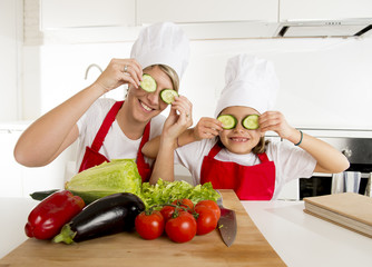 mother and little daughter cooking together playing with cucumber slices on the eyes