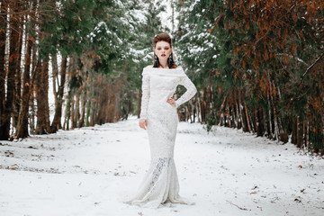 Bride in a long gown in the forest in winter