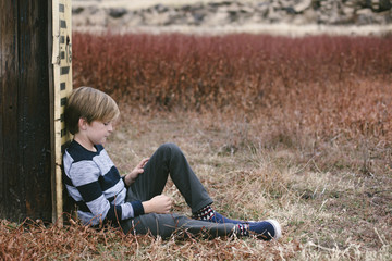 Side view of boy sitting on field by wood