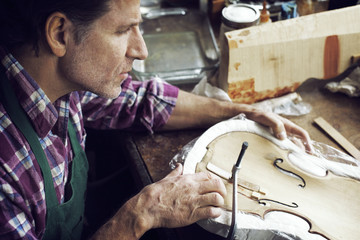 High angle view of man making violin in workshop