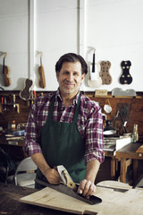 Portrait of worker standing in violin workshop