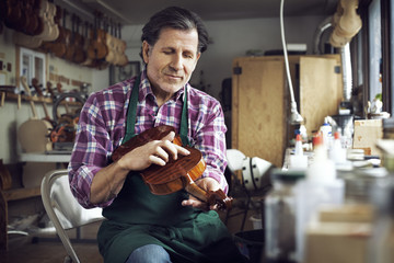 Worker touching violin while working in workshop