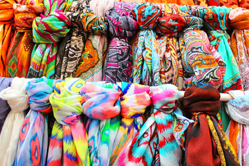 Rows of colourful silk scarfs hanging at a market stall in Tossa de Mar,Spain