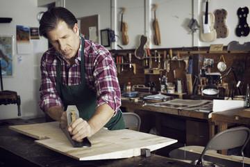 Man sawing wood while making violin in workshop