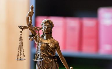 Justitia vor Bücherregal mit Gesetzbüchern