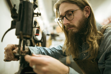 Serious shoemaker adjusting sewing machine at workshop