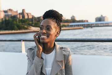 Happy woman talking on smart phone while sitting by railing against river