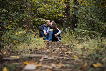 Couple kissing while sitting on field in forest