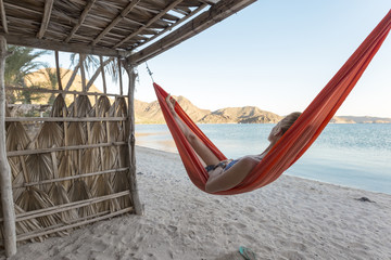 Woman relaxing in hammock on shore at beach