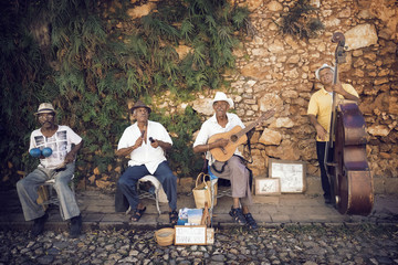 Street musicians playing musical instruments against stone wall
