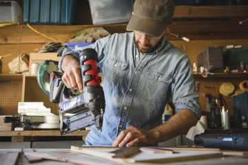 Artist using nail gun on wooden art at workshop