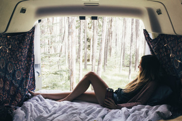 Woman looking through window while relaxing in camper van