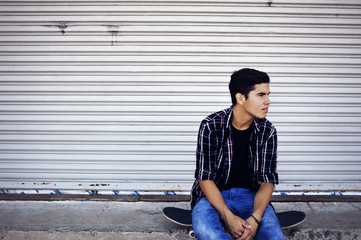 Man looking away sitting on skateboard against closed shutter