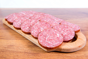 Close-up of chopped smoked sausage on a wooden board.
