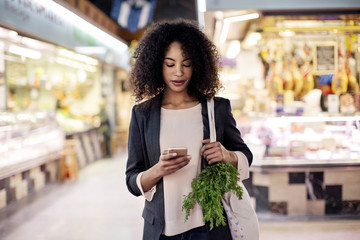 Woman using mobile phone while shopping in market