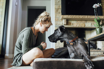 Woman looking at Great Dane while sitting at home