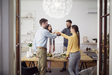 Friends raising celebratory toast while standing by dinning table in lunch party
