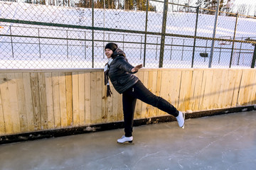 Girl skates at the rink in the winter time
