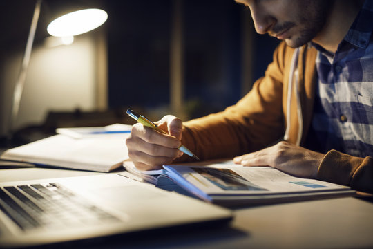 Man studying while sitting in library at night