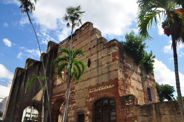 Old historical ruins of building with palm trees in Dominican Republic