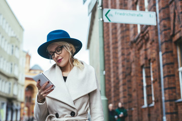 Low angle view of woman using mobile phone while standing on city street