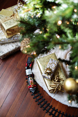High angle view of Christmas presents and miniature train on hardwood floor