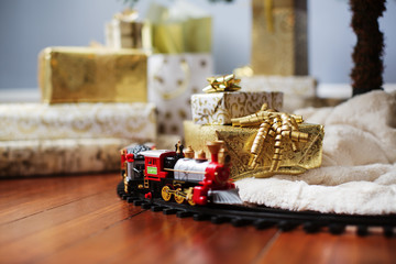 Miniature train and gift boxes on hardwood floor