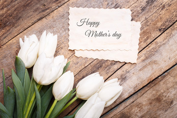 Happy mothers day card with tulips on wooden background