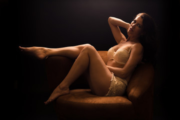 Young caucasian woman with brown hair and white lingerie reclines on a chair under a single light and looks at the viewer
