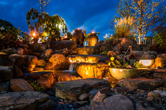 Waterfall fountain landscape at night with gold color lights and tiki