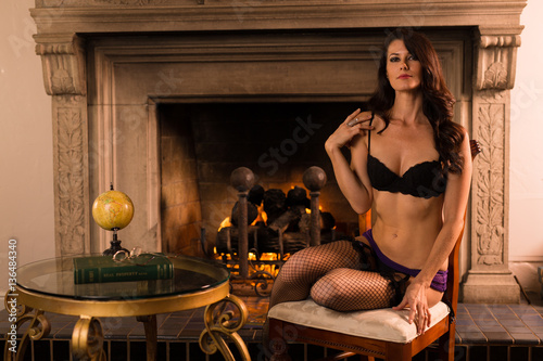 8e31fca2b3d Caucasian woman in lingerie sits by a fire in an elegant room
