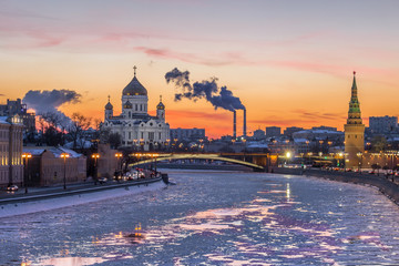 Cathedral of Christ The Savior, Moscow river, tower of Moscow Kremlin at frosty winter sunset. Smoke of power plants.