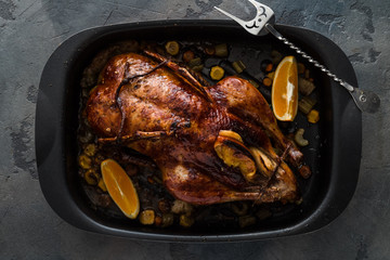 Roast duck with oranges and apples in a frying pan, dark photo, top view
