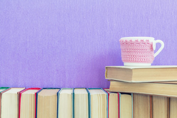 Books background. Many different books on violet wall. Cup of tea on books stack.