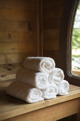 White spa towels rolled up in sauna