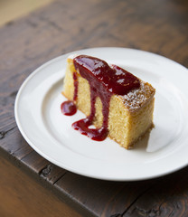 Slice of almond cake with berry sauce