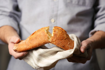 Male hands breaking freshly baked bread, closeup