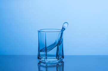 Splash in a glass of water on a blue background