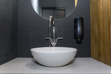 Water sink in restroom and mirror