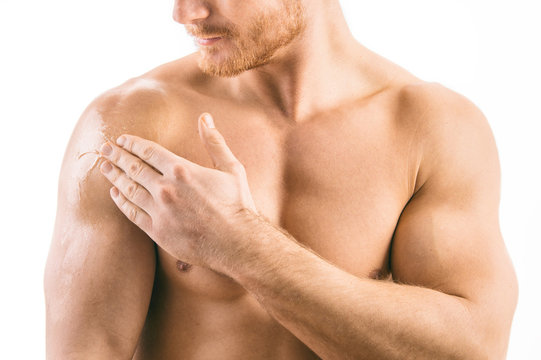 Testosterone Replacement Therapy (TRT) - Muscular man applying testosterone gel on shoulder