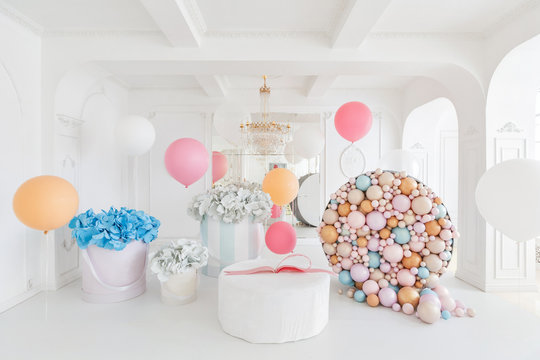 Boxes with flowers and a large pudrinitsa with balls and balloons in room decorated for birthday party.