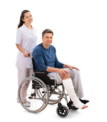 Female Nurse With Disabled Patient On Wheelchair