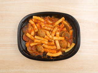 Top view of a rigatoni pasta with meatballs and sausage TV dinner atop a wood table.