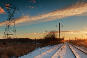 winter landscape transmission line on of bright red sunset