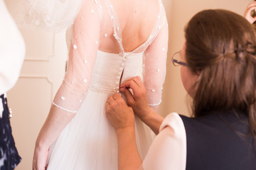 Woman helps the bride to try on a wedding dress
