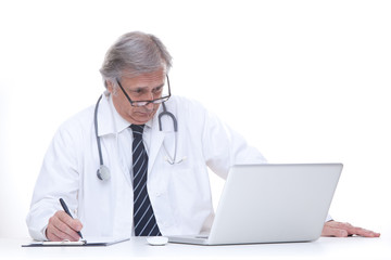 happy senior doctor with stethoscope working with laptop isolated on white