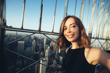 Young woman tourist laughing and taking selfie photo on Empire State Building in  New York City. Female traveler and photographer takes picture for her blog.