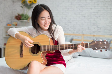Cute and happy smiling Asian girl playing acoustic guitar in bed