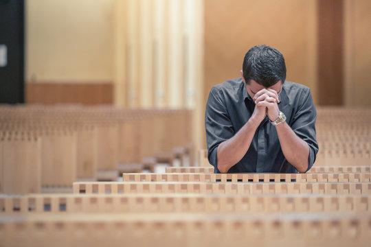 Young beard man wearing blue shirt praying in modern church