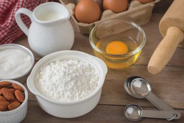 Baking ingredients flour, egg, milk, almonds, sugar on table
